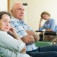 Tired elderly couple and disabled person on chair indoor. Focus on woman