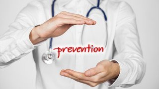 Healthcare prevention doctor (general practitioner) concept. Doctor with protective gesture and text prevention.