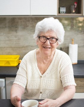 Happy smiling senior woman with cup of tea or coffee in the kitchen.