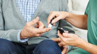 Krankenschwester macht eine Blutzuckermessung bei Patient mit Diabetes im Pflegeheim