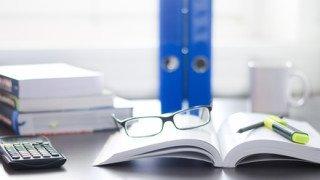 Schreibtisch / Arbeitsplatz mit Bchern, Brille, Taschenrechner und Ordnern