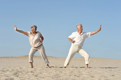elderly couple in love practicing karate against the sky