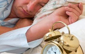 Ringing alarm clock and sleepy pensioner looking at it