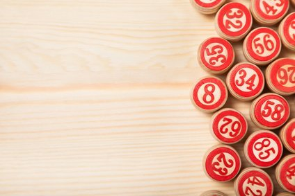Bingo lotto on wooden background with copy space. Balls with bingo numbers. Flat lay.
