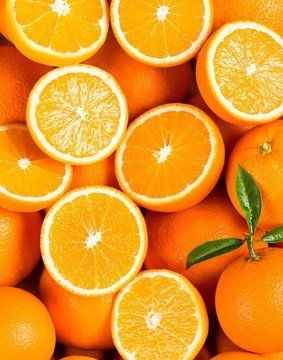 Background from sweet fresh whole and halves of orange fruits with green leaves.
