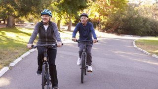 Front View Of Senior Couple Cycling Through Park Together